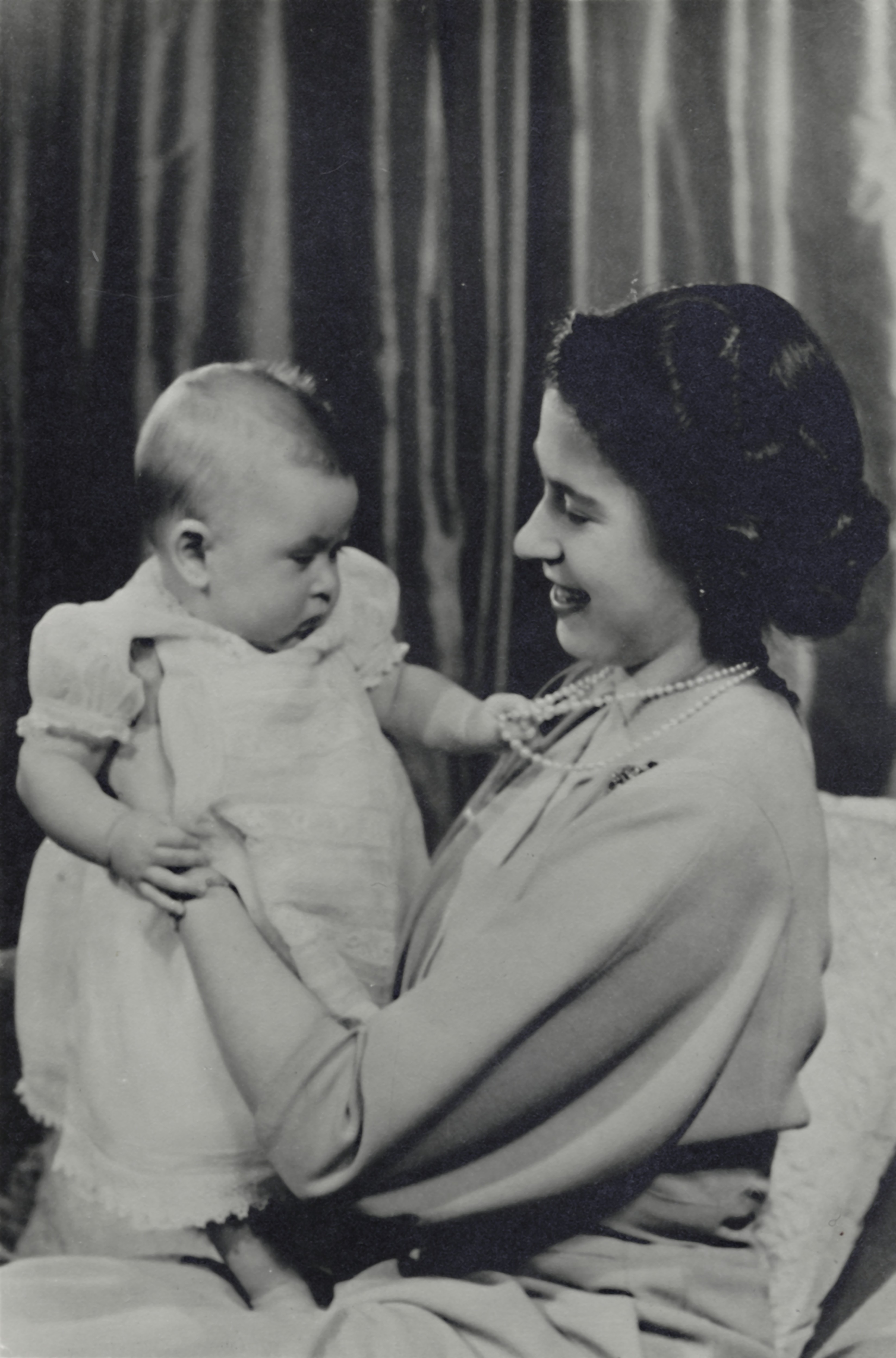 Princess Elizabeth with son, Prince Charles in 1948. Prince Charles is wearing a classic infant gown with lace trim.